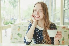 La muchacha sienta y bebe el café fotos de archivo libres de regalías