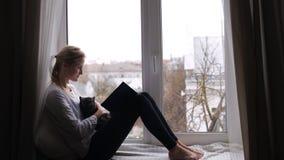 La muchacha sienta y lee un libro almacen de metraje de vídeo