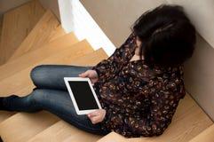 La muchacha sienta y mira la pantalla de la tableta, lee las noticias Trabajo en casa Mujer de negocios en casa en el ordenador imagenes de archivo