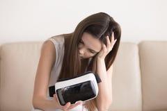 La muchacha siente mareada después de usar los vidrios de VR, sicknes de la realidad virtual Imagen de archivo