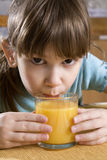 La muchacha siete años bebe el zumo de naranja Fotografía de archivo