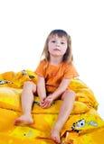La muchacha soñolienta se sienta en la cama imagenes de archivo
