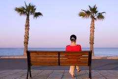 La muchacha sola se sienta en un banco Fotografía de archivo libre de regalías