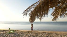 La muchacha sola toma el sol en una playa cerca del mar HD almacen de video