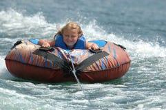 La muchacha sonríe a bordo del tubo del agua Imagenes de archivo