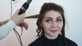 La muchacha sonríe en la cámara durante el peinado almacen de metraje de vídeo