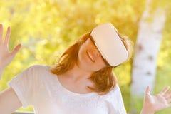 La muchacha sonríe en el casco de la realidad virtual Foto de archivo libre de regalías
