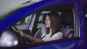 La muchacha sonríe en nuevo coche almacen de video