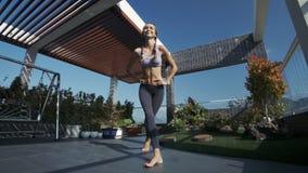 La muchacha sonríe ocupación con las piernas cruzadas en tejado