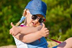 La muchacha sonríe y muestra como dos manos contra la perspectiva de árboles verdes fotos de archivo