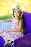 La muchacha sonríe y presenta en una silla al aire libre fotos de archivo