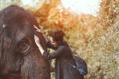 La muchacha sonriente abraza un elefante foto de archivo libre de regalías