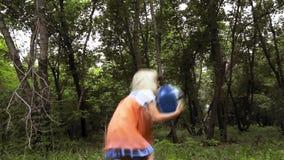La muchacha sonriente alegre juega con una bola almacen de metraje de vídeo