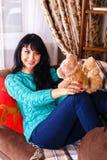 La muchacha sonriente alegre que se sentaba en el sofá en la Navidad adornó la internacional Foto de archivo