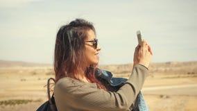 La muchacha sonriente atractiva joven de la raza mixta toma la foto panorámica del desierto en un teléfono móvil Mujer turística  metrajes