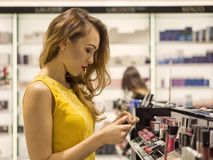 La muchacha sonriente atractiva joven en vestido amarillo está eligiendo el nuevo lápiz labial en tienda de los cosméticos Fotografía de archivo