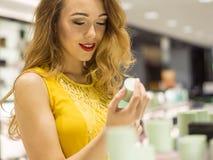 La muchacha sonriente atractiva joven en vestido amarillo está probando olor del nuevo perfume en la alameda de compras Imagenes de archivo