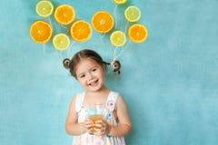 La muchacha sonriente bebe el zumo de naranja fresco Foto de archivo libre de regalías