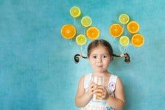 La muchacha sonriente bebe el zumo de naranja fresco Imágenes de archivo libres de regalías