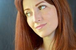 La muchacha sonriente blanca con el pelo rojo y los ojos verdes con extensiones de la pestaña en un fondo oscuro mira a la derech imagen de archivo