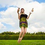La muchacha sonriente bonita está saltando en prado verde Imagen de archivo libre de regalías