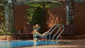 La muchacha sonriente cae en el agua que se sostiene a la barandilla
