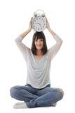 La muchacha sonriente con el reloj en la cabeza en loto presenta Imagen de archivo libre de regalías