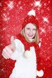 La muchacha sonriente con el sombrero de santa manosea con los dedos para arriba Fotos de archivo