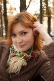 La muchacha sonriente con la bufanda florida en otoño estaciona Fotos de archivo