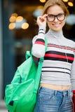 La muchacha sonriente con la mochila ajusta los vidrios Imagen de archivo