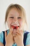 La muchacha sonriente con las frambuesas en su boca imagenes de archivo
