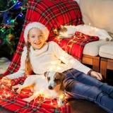 La muchacha sonriente con los animales domésticos acerca al árbol de navidad en casa Foto de archivo