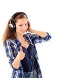 La muchacha sonriente con los auriculares manosea con los dedos para arriba Imagen de archivo