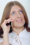 La muchacha sonriente con un teléfono móvil Fotos de archivo