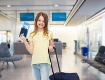 La muchacha sonriente con viaje empaqueta el boleto y el pasaporte Imagen de archivo libre de regalías