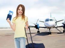 La muchacha sonriente con viaje empaqueta el boleto y el pasaporte Imagen de archivo