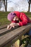 La muchacha sonriente de la edad de escuela está en el parque Foto de archivo