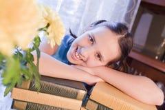 La muchacha sonriente de la escuela está cerca de los libros Fotografía de archivo