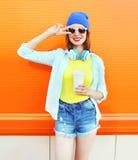 La muchacha sonriente de la moda con una taza de café es escucha la música sobre naranja colorida Imágenes de archivo libres de regalías