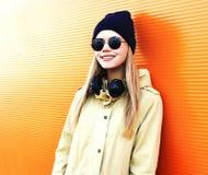 La muchacha sonriente de la moda en estilo negro con los auriculares escucha música sobre fondo colorido Fotos de archivo
