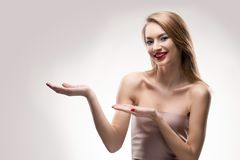 La muchacha sonriente de los labios rojos rubios hermosos lleva a cabo el spac vacío de la copia Imágenes de archivo libres de regalías