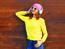 La muchacha sonriente de la moda escucha la música en auriculares Imagen de archivo libre de regalías
