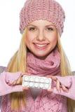 La muchacha sonriente del adolescente en sombrero del invierno y la bufanda que muestra píldoras embalan Fotografía de archivo