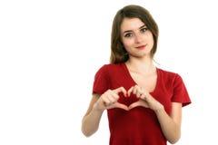 La muchacha sonriente del adolescente que hace el corazón forma con sus manos Imagenes de archivo