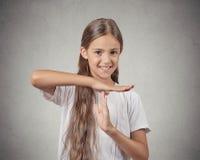 La muchacha sonriente del adolescente que muestra tiempo hacia fuera gesticula Foto de archivo libre de regalías