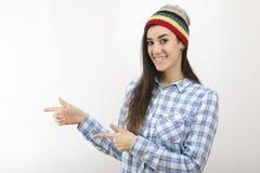 La muchacha sonriente del inconformista con el sombrero está señalando Fotos de archivo