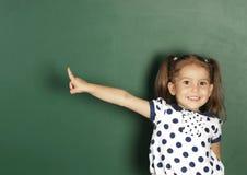 La muchacha sonriente del niño muestra con una pizarra de la escuela del espacio en blanco del finger, c imagen de archivo