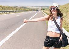 La muchacha sonriente del viajero está haciendo autostop a lo largo de una carretera Imagenes de archivo
