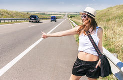 La muchacha sonriente del viajero está haciendo autostop a lo largo de una carretera Imagen de archivo