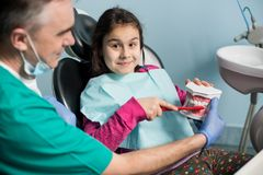 La muchacha sonriente en dentista preside sentarse con su dentista pediátrico, mostrando el diente-cepillado apropiado Foto de archivo libre de regalías